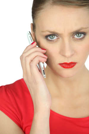 disillusioned: Annoyed woman in red using a cellphone