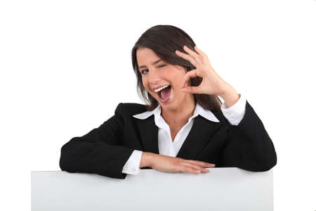 chirpy: Cheeky young woman in a suit giving the OK sign with a blank board ready for text