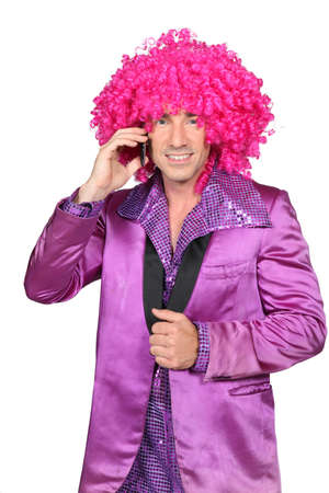dress suit: Man in Seventies costume and crazy wig on cellphone Stock Photo