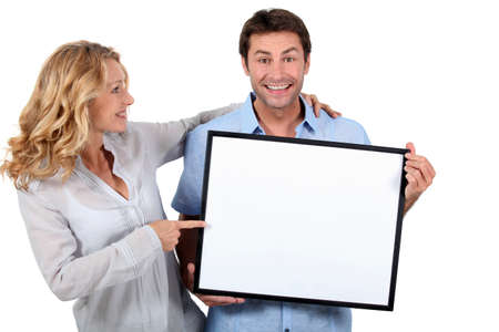 35 39 years: Smiling man and woman pointing at a blank board ready for your message