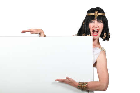 exclaiming: Woman dressed as Cleopatra pointing to a blank sign