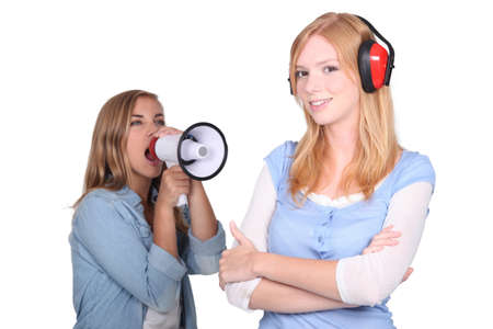 anti noise: girl shouting in loudspeaker at female workmate Stock Photo