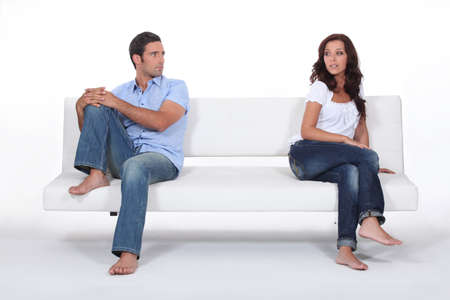 the opposite: couple sitting apart in couch after quarrel Stock Photo