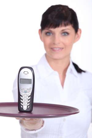usher: Waitress holding mobile telephone on tray