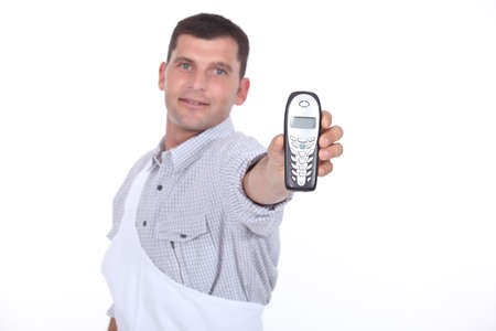 Dark haired man holding out mobile telephone photo