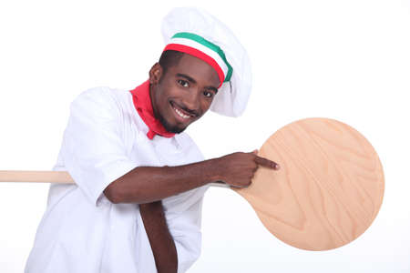 Pizza maker pointing to a pizza peel photo