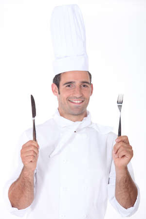 chefs whites: Chef in whites holding a knife and fork
