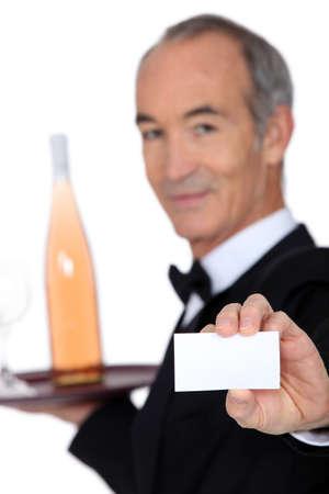 wine trade: Wine steward showing a business card