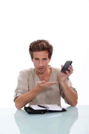 Man with a personal organizer demonstrating cellphone Stock Photo - 16472239
