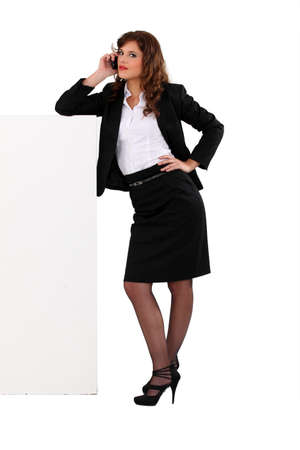 suit skirt: Businesswoman talking on her mobile phone and leaning against a blank sign Stock Photo