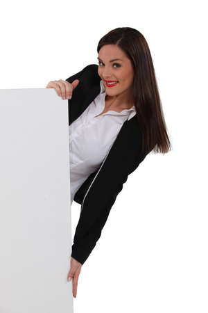 eagerness: Attractive woman holding a blank sign