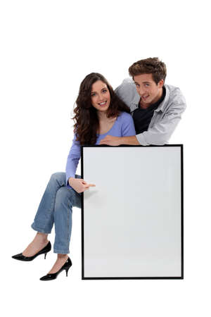 Young couple with a large picture left blank for your message photo