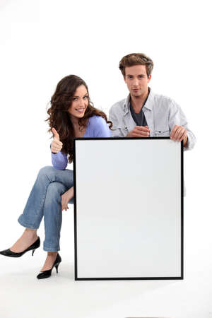 Couple sitting with a blank board photo