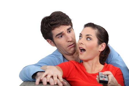 jointly: Shocked couple with a remote control