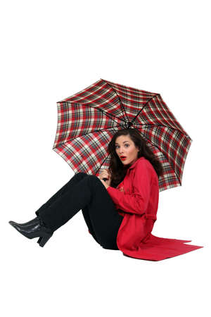 blown away: Woman blown over with her umbrella Stock Photo