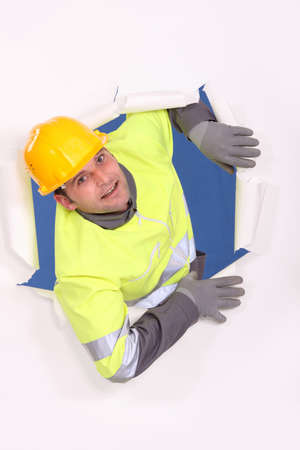 A male construction worker who went through a wall of paper  photo