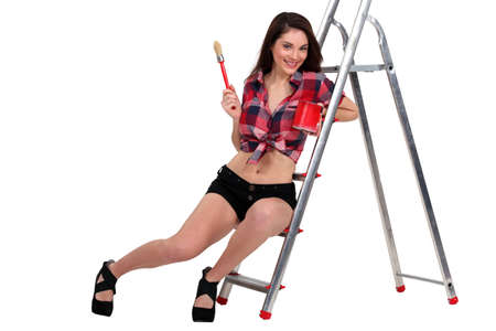 scaling ladder: Sexy woman sat on ladder holding paint pot