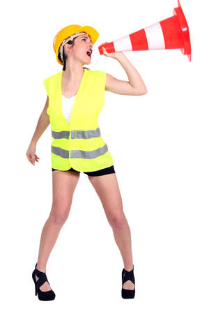 Attractive female construction worker shouting into traffic cone