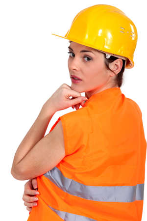 high visibility: Tradeswoman wearing a hart hat and an orange vest