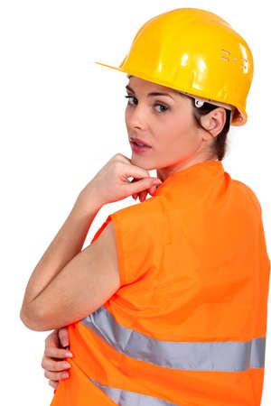 workwoman: Tradeswoman wearing a hart hat and an orange vest
