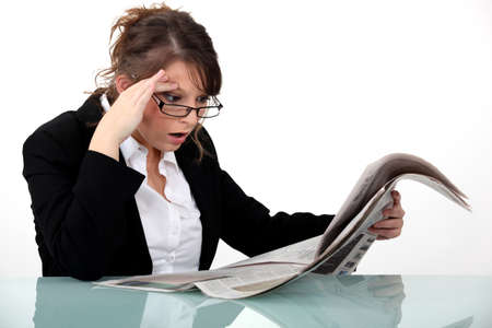 disbelief: Woman staring at the newspaper in disbelief