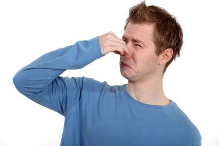 nariz: Hombre que sostiene su nariz contra el mal olor Foto de archivo