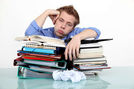 over burdened: Bored businessman leaning on a stack of files Stock Photo