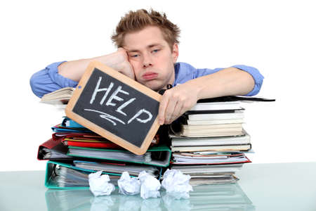 overloaded: student swamped under work Stock Photo