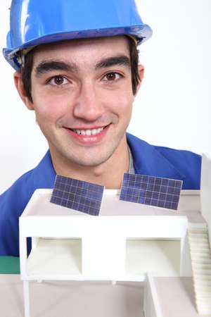 Young worker with an architectural model showing solar panels photo