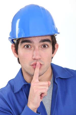 shushing: Young manual worker shushing