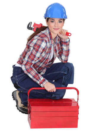 tradeswoman: Portrait of a tradeswoman with a pipe wrench and a toolbox Stock Photo