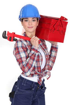 solucion de problemas: Un obrero femenino con una caja de herramientas y una llave