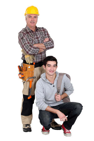 20 to 25 years old: Experienced tradesman posing with his new apprentice