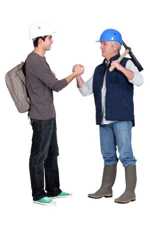 craftsman and apprentice shaking hands Stock Photo - 16472228