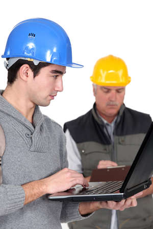 young craftsman working on his laptop while senior craftsman is taking notes photo