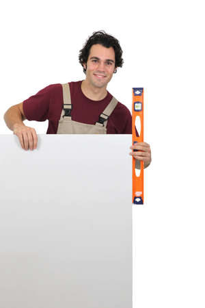 public spirit: Handyman with poster and spirit-level Stock Photo
