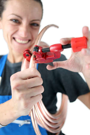 Female plumber cutting copper pipe Stock Photo - 16548144