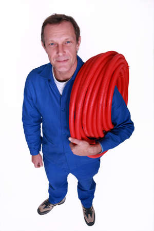 flexi: Plumber with large reel of red flexible pipe