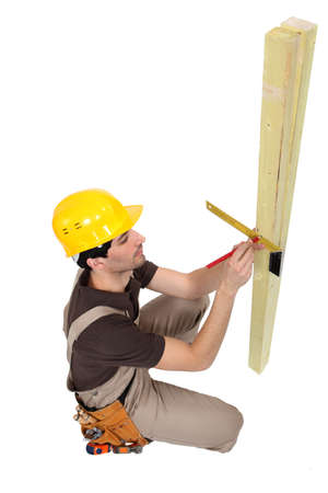 kneeled: Carpenter marking wood Stock Photo