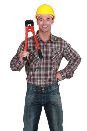 portrait of young craftsman holding adjustable spanner photo