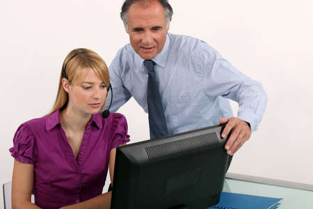 25 years old: Woman and her boss at a computer Stock Photo