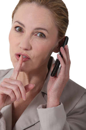 exasperate: Woman indicating quiet whilst holding a phone Stock Photo
