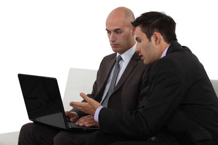 decipher: Businessmen discussing something on a laptop