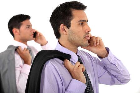 mirror image: Businessmen with phones