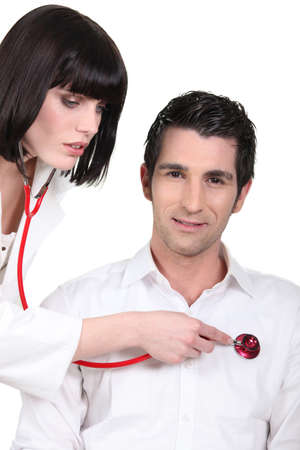 Attractive female doctor listening to her male patient's heartbeat Stock Photo - 16555018