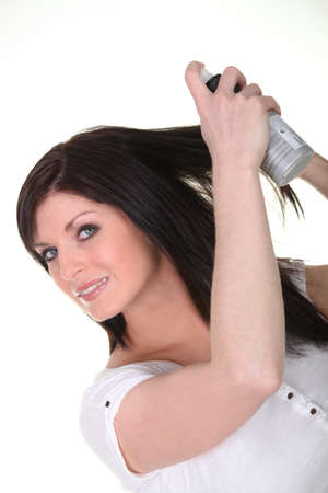 smoothen: Woman spraying a beauty product into her hair Stock Photo
