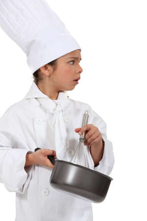 little girl dressed as a chef holding a whisk photo