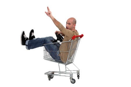 shopping buggy: Man in a shopping trolley Stock Photo