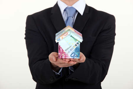 dwelling: Businessman holding a house made of money Stock Photo
