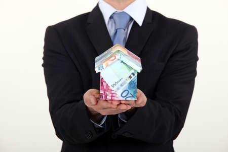 banconote euro: Uomo d'affari in possesso di una casa fatta di soldi